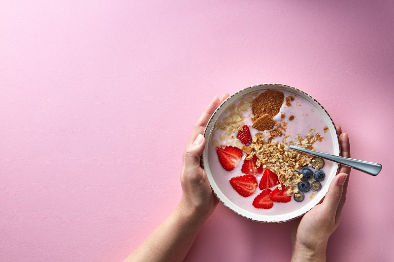 Healthy smoothie in white bowl with natural fruits oat flakes and biscuits with woman's hands holding a bowl on pink background. Superfoods natural detox diet and healthy food. Flat lay photo