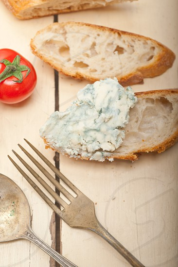 fresh blue cheese spread ove french baguette with cherry tomatoes on side photo
