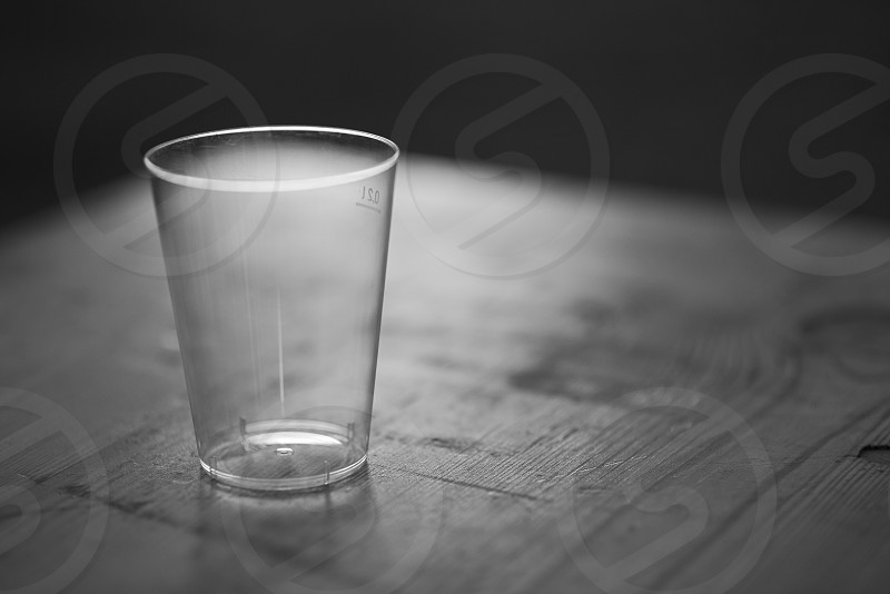 Empty Clean Backlit Plastic Cup on a Wooden Table at Night Closeup photo