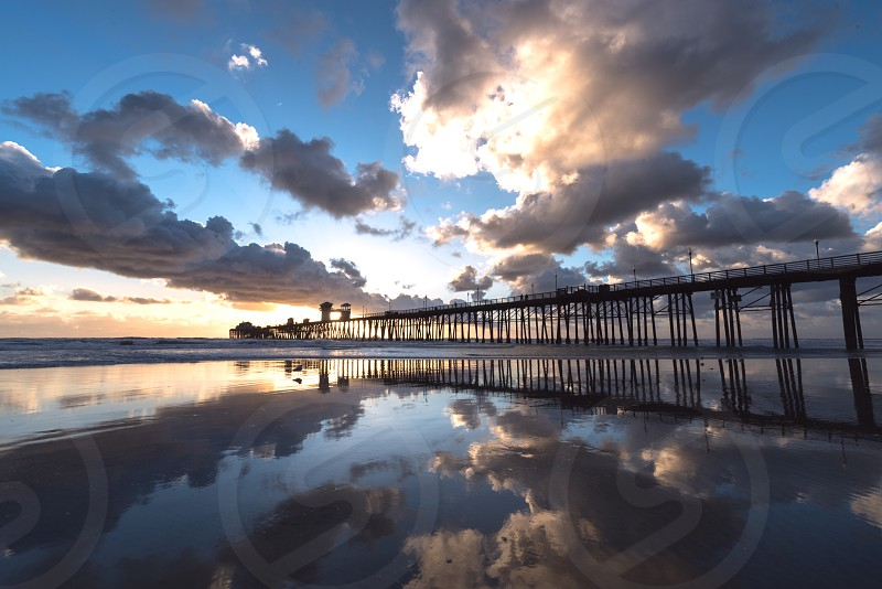 Clouds sky low tide reflection pier  photo