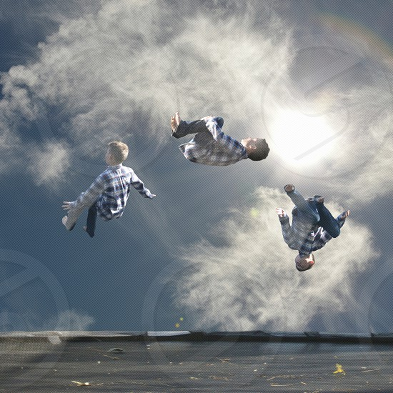 3 boys wearing blue and white checked sports shirts jump in different position under white and blue sky photo