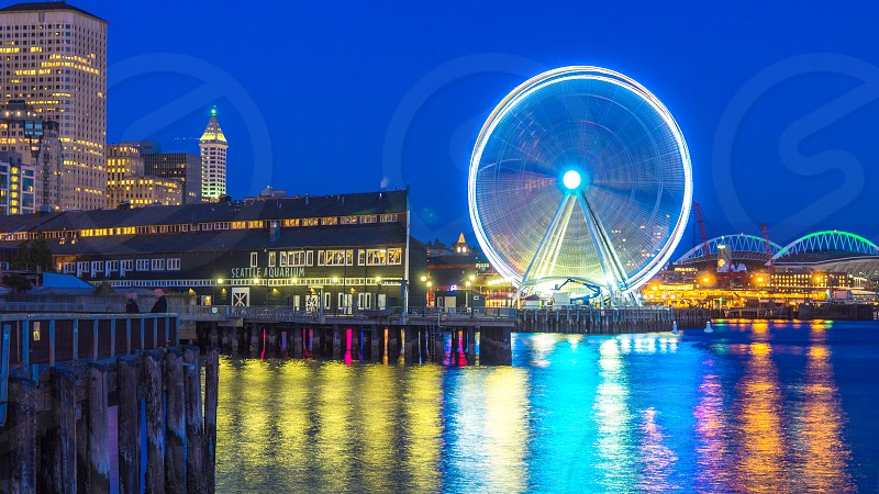 time lapse photography of urban view near body of water with ferry's wheel photo