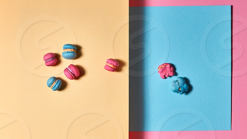 Set of blue and pink macaroons one macaroon crushed on a pink yellow paper background. Flat lay photo