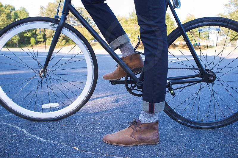 Person Wearing Blue Cuffed Pants and Brown Boots On Bike photo