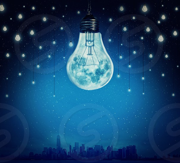 Moon and stars in shape of bulbs light over a city. Surreal background. Alternative energy concept photo
