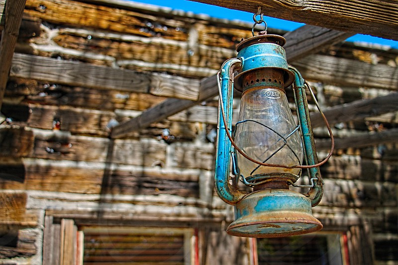 Rustic blue vintage lantern hangs on a pole in front a blurred background of a wooden rural house. photo