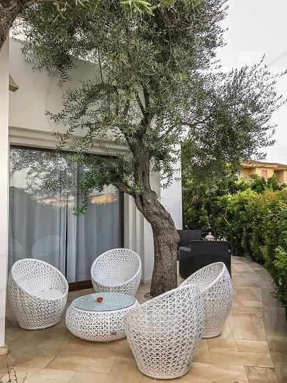 #backyard #backyards #courtyard #yard #outdoors #bush #tree #chair #table #patio #house #villa #countryhouse #wicker #furniture #wickerfurniture #streetfurniture  photo