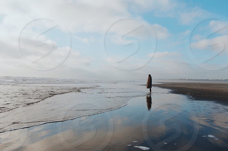 person draped in blanket standing in beach photo