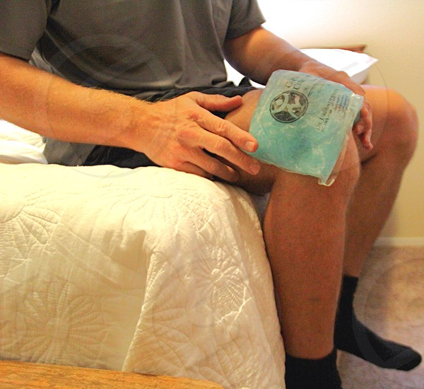 Man with knee pain ice pack on knee photo