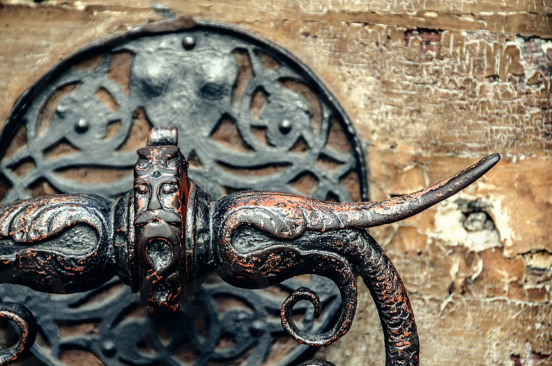 An Asian-style door knocker on an old wooden door. photo