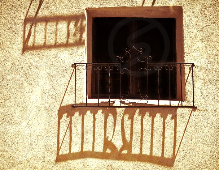 A small ornate window guard throws shadows on the building wall. photo