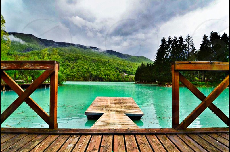 grey cloudy sky over green hills lining lake with brown wood rectangular dock with fence in green lake water photo