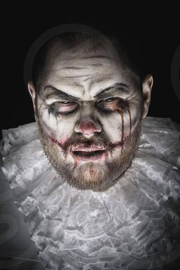 Portrait of a Scary Evil Clown.  Studio shot with horrible face art photo