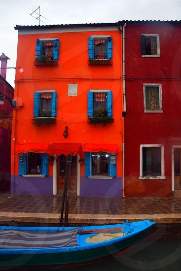 blue boat near orange and purple painted house photo