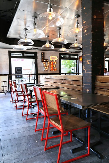 brown and red chairs under black pedestal square tables viewing wall mount love free standing letters under transparent glass pendant light inside the pub photo
