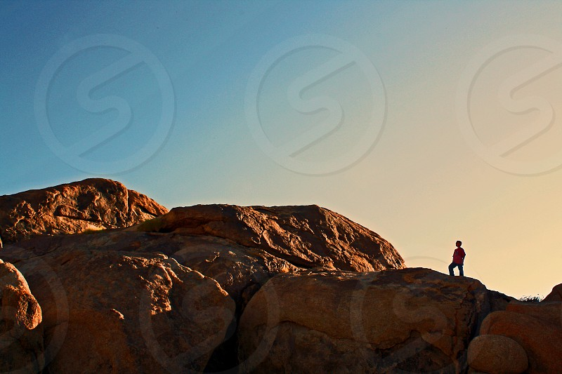 A boy stands on top of huge boulders back lit by a setting sun. photo
