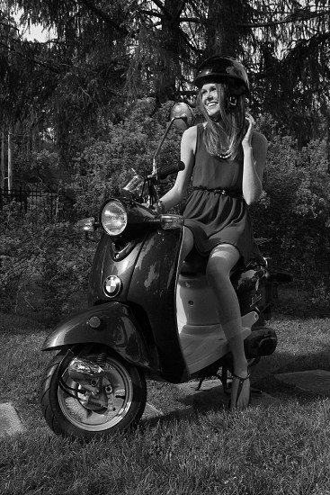 Urban girl ready to ride her Vespa.  photo