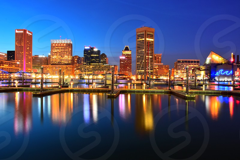 reflection of city high rise buildings and lights on calm body of water under blue clear sky photo