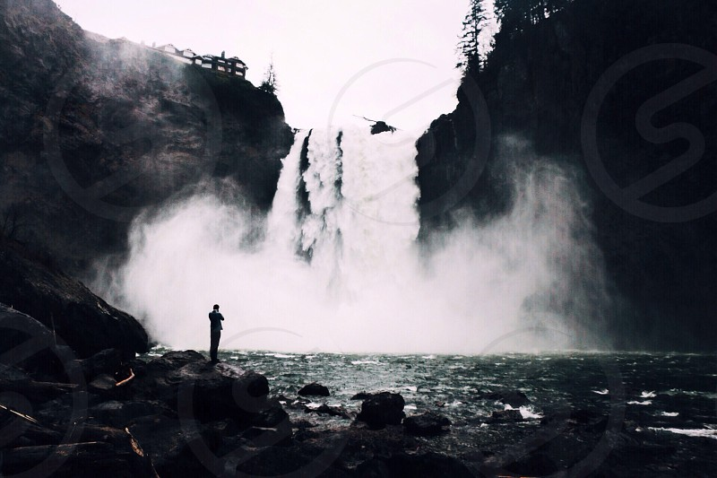 man standing on rock watching falls photo