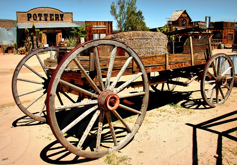 Large wooden wagon holds a bale of hay in a rustic western town photo