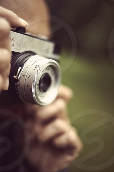 Close up of a photographer shooting with a vintage plastic Russian 35mm film camera on location photo