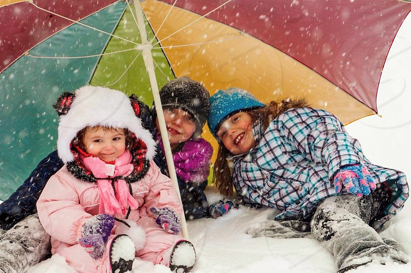 three girls wearing winter jackets sitting on snow covered ground under yellow red and green umbrella photo