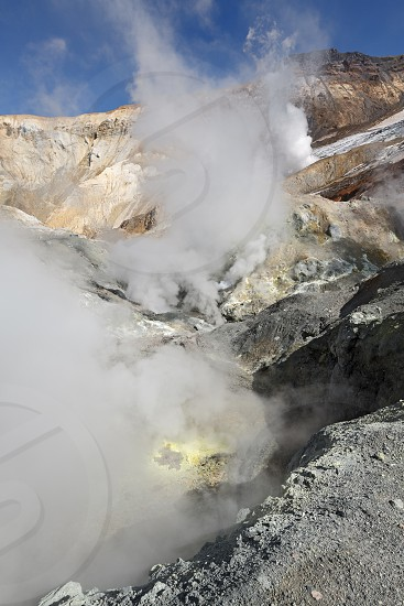 Volcanic landscape of Kamchatka: brimstone and fumarole field in crater of active Mutnovsky Volcano. Russia Far East Kamchatka Peninsula. photo