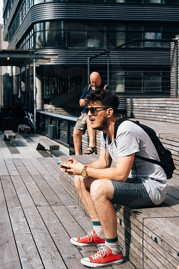 Unidentified man with smartphone sitting on steps in High Line. The High Line is an elevated linear park greenway and rail trail. It was created on a former New York Central Railroad spur on the west side of Manhattan photo