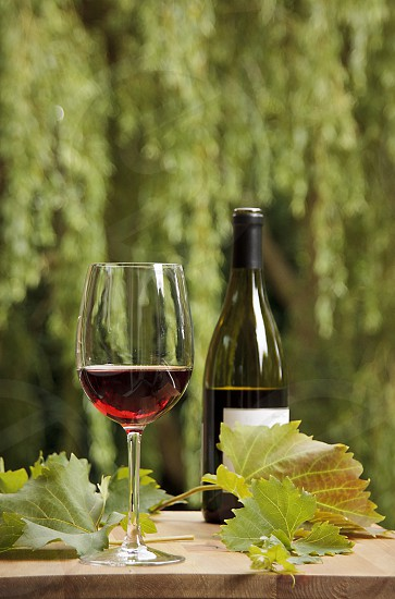 Still life of a glass and bottle of wine with vine leaves photo