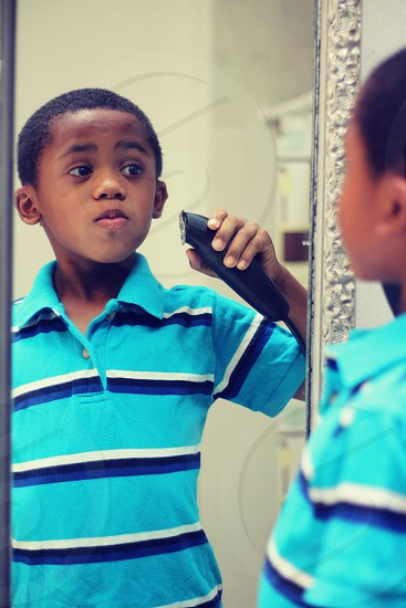 boy in blue white black stripe polo shirt standing in front of mirror holding hair clipper against face photo