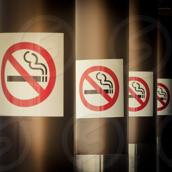 Series of No Smoking signs mounted on columns of airport building with diminishing perspective for a healthy smoke free environment photo