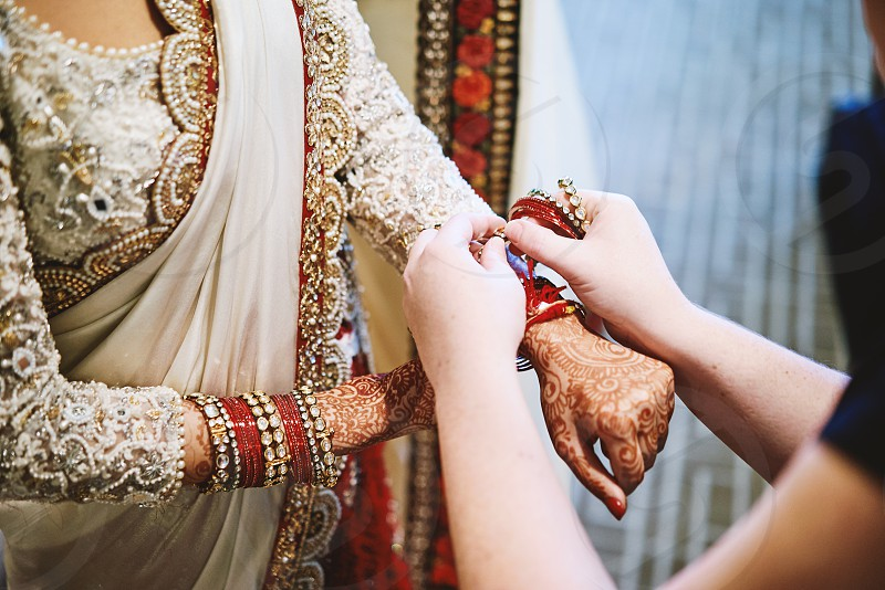 Family tying auspicious thread on wrist of the Indian bride during the thread ceremony of Indian Hindu wedding. photo