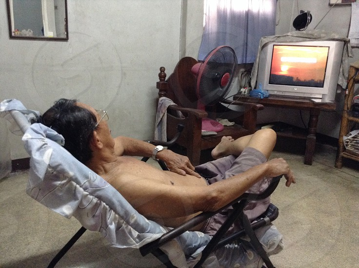 Thai old man see television photo