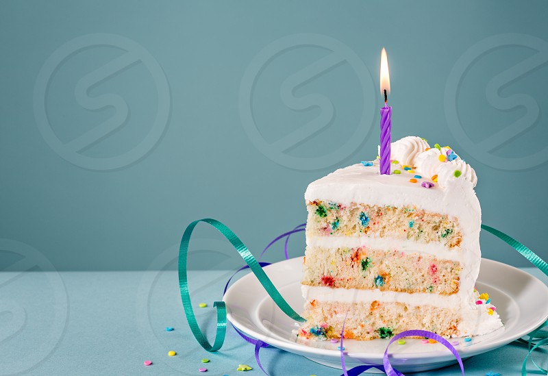 Slice of Birthday Cake with a lit candle and ribbons over a blue background. photo