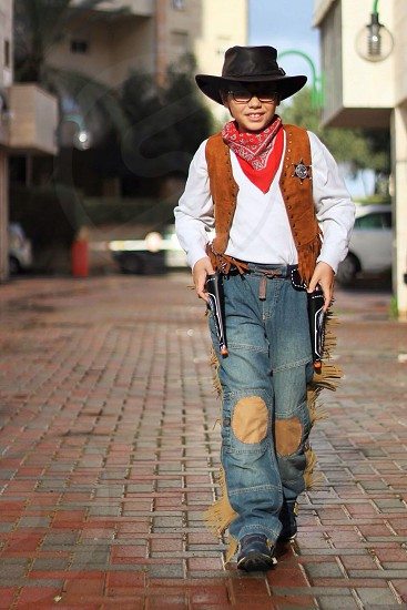 boy in cowboy outfit walking on bricked road photo