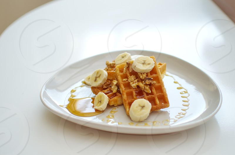 Whole grain waffles with Pecansmaple syrup and bananas for a healthy breakfast photo