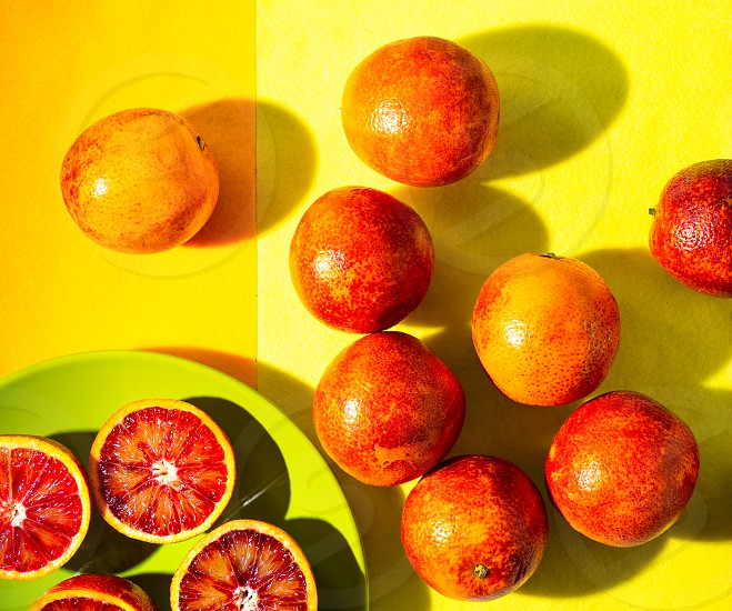 Fresh whole and cut blood oranges on yellow colored background photo