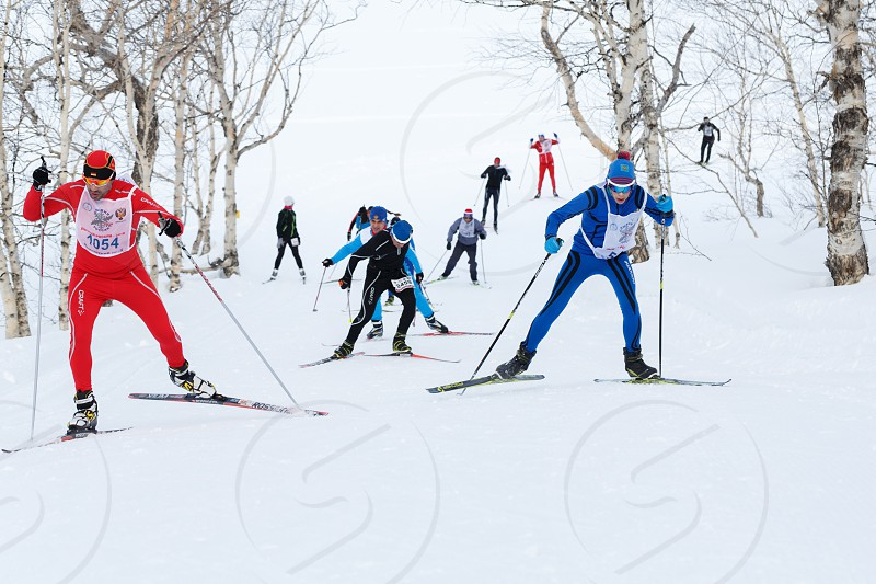 PETROPAVLOVSK CITY KAMCHATKA PENINSULA RUSSIAN FAR EAST - FEBRUARY 10 2018: Skiers running on ski track in cross-country winter forest. All-Russia mass ski race - Ski Track of Russia. photo