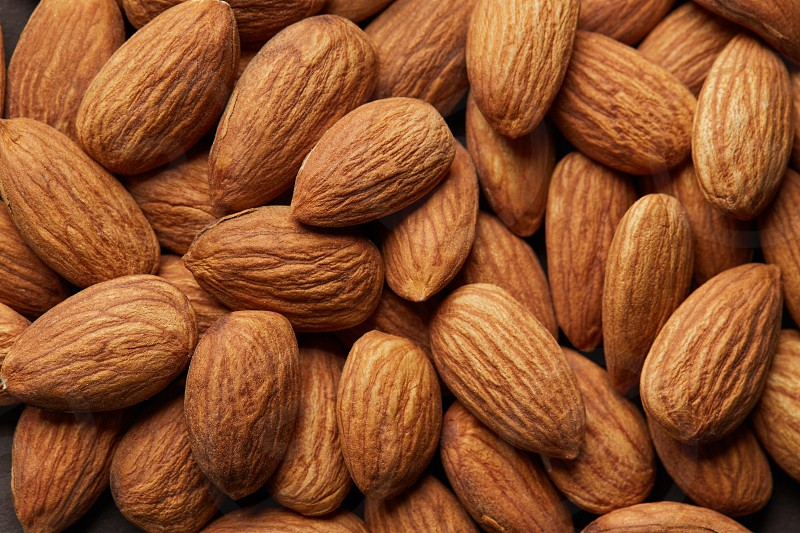 Background of pile brown almond macro top view. Food healthy concept photo