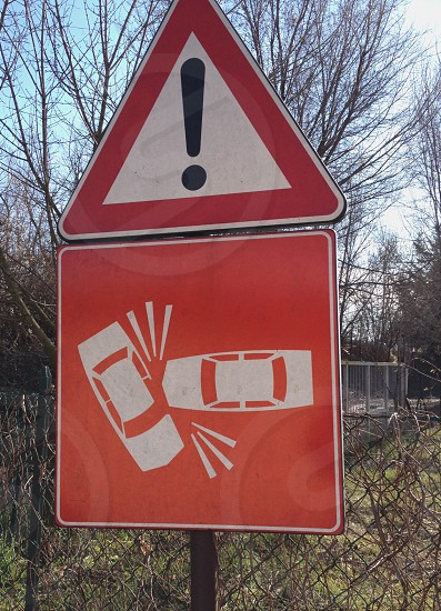 warning exclamation sign with vehicles crashing road sign against chain link fence under bare trees photo