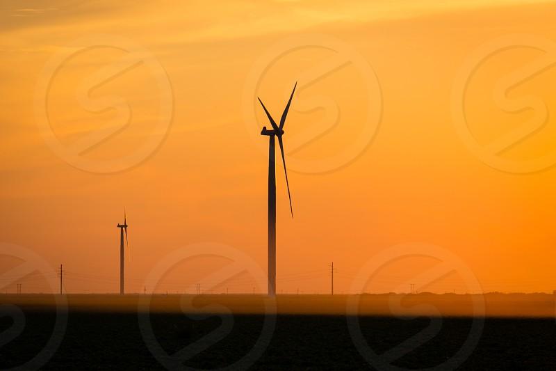 wind turbines against orange sky photo