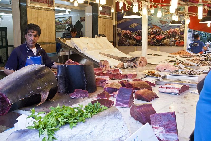 man in blue apron standing near tuna on market stall photo