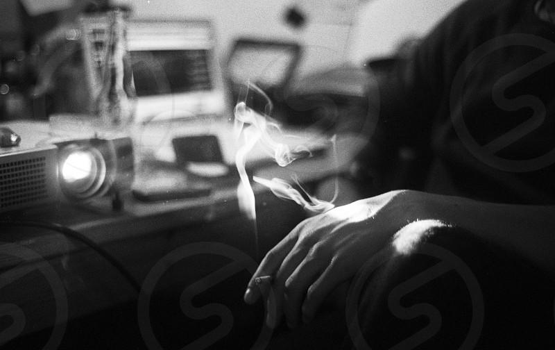 smoke hand friends black white film projector catching light cigarette photo