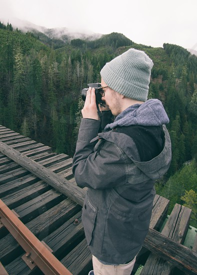 man in grey hoodie taking picture standing on train way photo