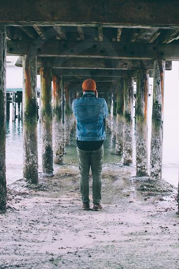 man in denim jacket and red hat under dock pier photo