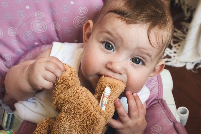 Cute baby girl playing with her brown teddy bear soft toy and chewing on the bear's foot photo