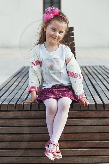 Portrait of cute adorable little girl sitting on bench in the center of town smiling and looking at camera. Candid people real moments authentic situations photo
