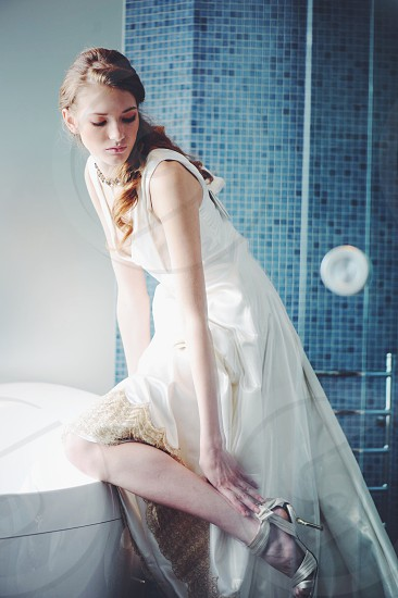 woman in white sleeveless dress looking and touching her left ankle photo