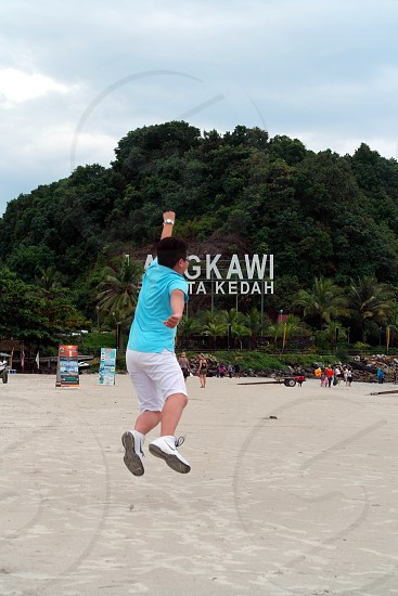 man wearing teal shirt trying to get jump shot with superman post on white sand during daytime photo