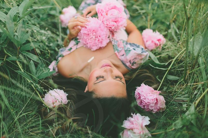 A beautiful woman lying in a peony field.  photo